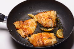 Fish cooking in frying pan Stock Photo