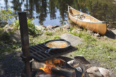 Fish Cooking Outdoors In A Frying Pan With A Canoe In The Backgr Stock Images