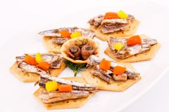 Fish on crackers. Fish and peppers on crackers  on white plate Royalty Free Stock Photo