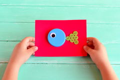 Fish crafts. Child holding a cardboard with craft fish. DIY bottle caps. Creative bottle cap ideas. Recycle crafts. Project to make from recycling bottle caps Royalty Free Stock Image