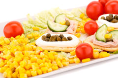 Fish cream in pastries. Sweet corn, cherry tomato and lettuce on white plate Stock Photo