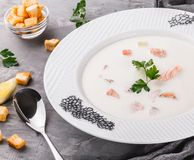 Fish cream soup with fillet salmon and shrimps, parsley in plate over rustic background, healthy food. Ingredients on table.  royalty free stock photo