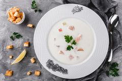 Fish cream soup with fillet salmon and shrimps, parsley in plate over rustic background, healthy food. Ingredients on table. Top view, flat lay royalty free stock photo