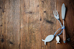 Fish cutlery tied with empty fish shaped tags. Fish cutlery tied with empty fish shaped tag on wooden table with copy space. Menu card for restaurants Royalty Free Stock Image