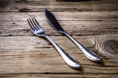 Fish cutlery on wooden table Stock Photos