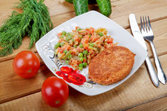 Fish cutlet with vegetables on a  table Stock Photos