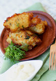 Fish Cutlets. Delicious Breaded Fish Cutlets with Garlic, Greens and Tartar Sauce on Brown Plate with Wooden Fork closeup on Green Napkin. Selective Focus Royalty Free Stock Images
