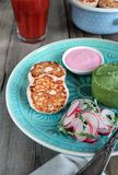 Fish cutlets with green mashed potatoes. pink sauce and radish and microgreens salad. tomato juice royalty free stock photography