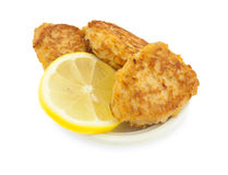 Fish cutlets with a lemon on the white plate. Royalty Free Stock Images