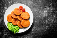 Fish cutlets on a plate with salad leaves and tomatoes. On black rustic background royalty free stock photo