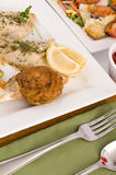 Fish dinner. Plates of baked fish and garden salad with a glass of red wine and strawberry dessert Royalty Free Stock Photo