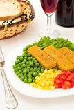 Fish Dinner. Fish fingers with vegetables and a glass of wine stock image