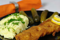Fish dinner. Fish with smashed potatoes and pickles on the side dinner Royalty Free Stock Images