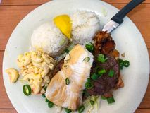 Healthy Fish Dinner with Rice. Fish dinner with lemon rice, pork and macaroni. Served under the heading of Aloha Mixed Plate - a traditional meal served in Royalty Free Stock Image