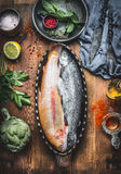 Fish dish cooking preparation. Two Trout fishes in baking form on wooden rustic kitchen table background with vegetables and condi. Ment ingredients, top view Stock Images