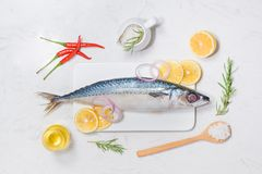 Fish dish cooking with various ingredients. Fresh raw fish decor. Ated with lemon slices and herbs on wooden table Royalty Free Stock Photos