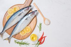 Fish dish cooking with various ingredients. Fresh raw fish decor. Ated with lemon slices and herbs on wooden table Stock Photo