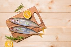 Fish dish cooking with various ingredients. Fresh raw fish decor. Ated with lemon slices and herbs on wooden table Stock Photos