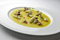 Fish Dish Cream of Jerusalem artichokes with saffron and squid. With Herbs in white plate Stock Photos