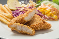 Fish dish - fried fish fillet with vegetables on black backgroun Stock Image