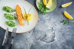 Fish dish with grilled salmon and lemon slice. Copy space. Fish dish with grilled salmon and lemon slice stock images