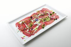 Fish dish, Red tuna carpaccio inspired by Pollock. Plate with Red tuna carpaccio inspired by Pollock royalty free stock photography