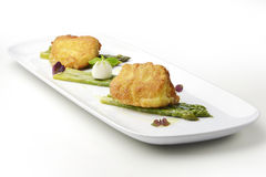 Fish dish Salt cod breaded Milanese style with asparagus Stock Photo