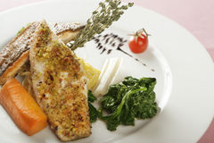 Fish dish with spinach. A selection of fish fillets served on a plate, garnished with vegetables and herbs Stock Photography