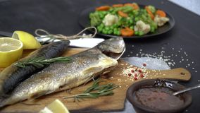Fried fish on a cutting board around scattered rosemary, lemon, sesame and red berries on a plate next side is a garnish. Fish dish with vegetable garnish stock footage