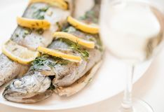 Fish dish on a white plate with glass of white wine. Fish dish with lemons and greenery on a white plate with glass of white wine for dinner stock photography