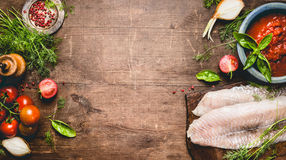Fish dishes cooking. Fresh raw fish fillet with tomatoes ,sauce and ingredients on rustic wooden background, top view, banner. Healthy or diet food concept Royalty Free Stock Photo