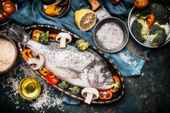 Fish dishes cooking preparation with dorado in backing form in shape of fish with healthy vegetables on dark rustic background wi. Th ingredients, top view Stock Photo