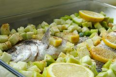 Fish dorado with vegetables and lemon. Uncooked fish dorado with vegetables and lemon Stock Photography