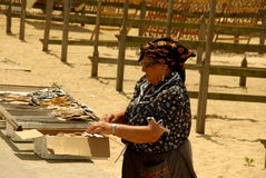Fish drying racks. Woman dressed with fishermans typical vests from Nazare spreads fish on racks to dry in the sun. Nazare, Portugal Stock Images