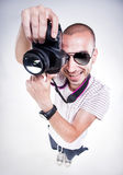 Fish eye shot of funny photographer posing with a camera smiling Stock Photos