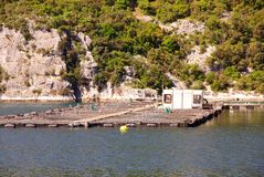 Fish farm. Rocks with in front a fish farm in the river Stock Photo