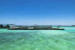 fish farm in the turquoise ocean with small waves, blue sky background. Royalty Free Stock Photos