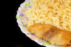 Fish filet with tagliatelle isolated on black. Fried fish filet with tagliatelle on plate isolated on black background royalty free stock photo