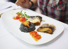 Fish fillet with black risotto and tomato relish Stock Photography