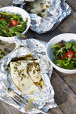 Fish fillet grilled in a piece of foil. On the wooden table stock image