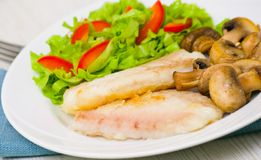 Fish fillet with mushrooms and salad Royalty Free Stock Photos