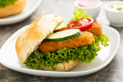 Fish fillet sandwich. Hearty fish fillet sandwich with salad and veggies Stock Photo