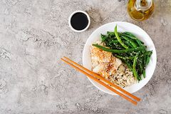 Fish fillet served with rice, soy sauce and green beans in white plate. Asian food. Top view. Flat lay stock image