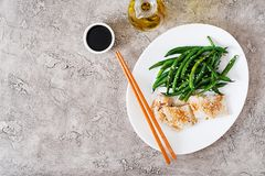 Fish fillet served with soy sauce and green beans in white plate. Asian food. Top view. Flat lay royalty free stock photos