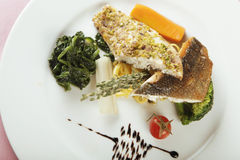 Fish fillet with spinach. Fish dish with spinach, a selection of fish fillets served on a plate, garnished with vegetables and herbs Royalty Free Stock Images