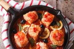 Fish fillet in tomato sauce in a pan closeup. horizontal top vie Stock Images