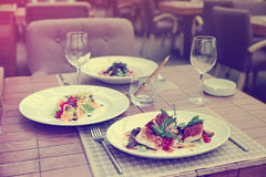 Fish fillet with vegetables and another food on table, toned Stock Image