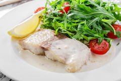 Fish fillet in white sauce stock photography