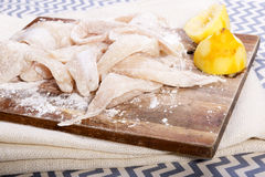 Fish Fillets. Fresh flathead fish fillets coated in flour ready for cooking with lemons Stock Photography