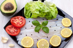 Fish fillets. With lemon, avocado, tomato and lettuce on black plate Royalty Free Stock Photo